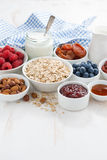 Oat flakes and various ingredients for breakfast on white. Wooden table, vertical, close-up Stock Photo