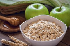 Oat flakes in white bowl with fresh green apple and honey Stock Photos