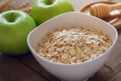 Oat flakes in white bowl with fresh green apple and honey Stock Photography