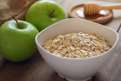 Oat flakes in white bowl with fresh green apple and honey Royalty Free Stock Photo