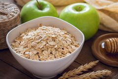 Oat flakes in white bowl with fresh green apple and honey Royalty Free Stock Images