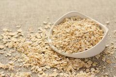Oat flakes in white ceramic bowl on sackcloth background Stock Image