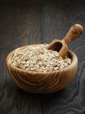 Oat flakes in wood bowl on oak table Stock Images