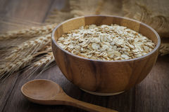Oat flakes in wooden bowl and wheat Stock Photo