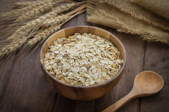 Oat flakes in wooden bowl and wheat Royalty Free Stock Image