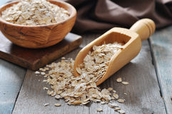 Oat flakes in wooden  scoop. On wooden background Stock Image