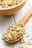 Oat flakes on a wooden spoon Royalty Free Stock Image