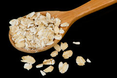 Oat Flakes in Wooden Spoon on Black Background Stock Image