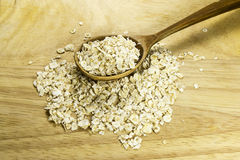 Oat flakes on a wooden spoon. This spoon with oat on wood background Stock Image