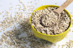 Oat flakes in a yellow bowl of a wooden spoon Stock Images