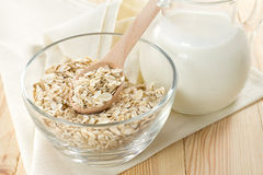 Oat flaks on a glass boel and jug of milk Royalty Free Stock Images