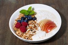 oat granola with apples and berries on wooden background stock photos