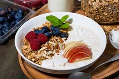 Oat granola with apples and fresh berries on wooden background. Closeup horizontal Stock Photos