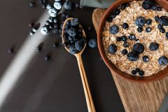 Oat granola with fresh blueberries and currants in a clay bowl over dark grunge surface. Top view, copy space. Wooden background. royalty free stock photos