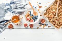 Oat granola with nuts, yogurt, honey, fresh figs and blueberries Stock Photo