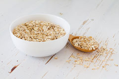 Oat meal in white bowl, wood background Stock Image