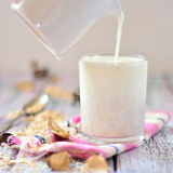 Oat milk in a glass on the table with fruit Royalty Free Stock Photo