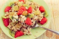 Oat muesli on fork, healthy breakfast. On green plate Stock Photo