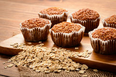 Oat muffins and flakes on brown wooden board. Royalty Free Stock Images