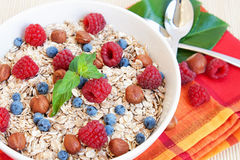 Oat nuts breackfast. Oat nuts with fresh blueberries and raspberries and hazelnuts Royalty Free Stock Photography