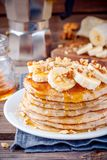 Oat pancakes with banana, walnuts and maple syrup. Breakfast oatmeal pancakes with banana, walnuts and maple syrup royalty free stock photography
