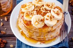 Oat pancakes with banana, walnuts and maple syrup closeup. Breakfast oatmeal pancakes with banana, walnuts and maple syrup closeup royalty free stock photography