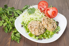 Oat Patty with vegetables, cabbage, tomato and peas. Laid out on a white plate, decorated with greenery Stock Photos