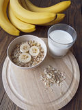 Oat porridge with bananas and yogurt on a  table whith milk. Oat porridge with bananas and yogurt on a wooden table Stock Photography