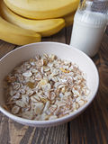 Oat porridge with bananas and yogurt. On a wooden table Stock Photography