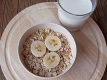 Oat porridge with bananas and yogurt. On a wooden table Royalty Free Stock Images