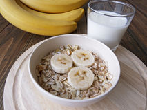 Oat porridge with bananas and yogurt. On a wooden table Royalty Free Stock Photos