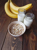 Oat porridge with bananas and yogurt. On a wooden table Stock Images
