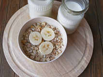 Oat porridge with bananas and yogurt. On a wooden table Royalty Free Stock Photo