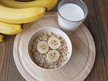 Oat porridge with bananas and yogurt. On a wooden table Stock Photo