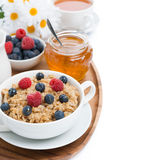 Oat porridge with berries and honey, black tea, isolated Stock Photo