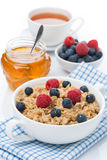 Oat porridge with berries and honey, a cup of black tea Royalty Free Stock Photo