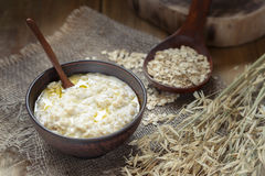 Oat porridge with butter in a clay bowl. Oatmeal with butter. Oatmeal in a clay bowl on burlap, low key, close-up stock photography