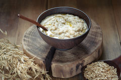Oat porridge with butter in a clay bowl. Oatmeal with butter. Oatmeal in a clay bowl on a wooden log, low key, close-up royalty free stock image