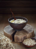 Oat porridge with butter in a clay bowl. Oatmeal with butter. Oatmeal in a clay bowl on a wooden log, low key, close-up stock image