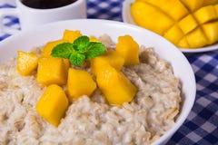 Oat porridge with fresh mango in the white bowl with coffee Royalty Free Stock Photos