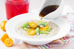 Oat porridge with fruit, orange, cumquat, kiwi, maple syrup Stock Photography