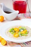 Oat porridge with fruit, orange, cumquat, kiwi, maple syrup Stock Photos