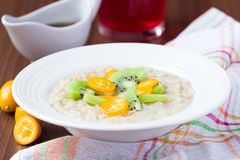 Oat porridge with fruit, orange, cumquat, kiwi, maple syrup Stock Image