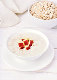 Oat porridge with red apple slices Stock Images
