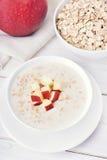 Oat porridge with red apple slices Stock Image