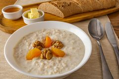Oat porridge. With walnuts and dried apricots served for breakfast with butter, honey and gray bread stock image