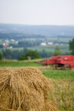 Oat Shock and Old Baler. Shock of oats with an old red baler in the background, overlooking a rural farming community royalty free stock photography