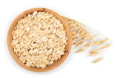 Oat spike with oat flakes in wooden bowl isolated on white background. Top view. Flat lay.  royalty free stock image