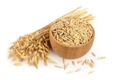 Oat spike with grains in wooden bowl isolated on white background.  Stock Photography