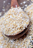Oat in a spoon on wooden background Stock Photos